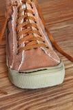 Single Gym shoe on wooden background taken closeup. Toned image royalty free stock photos