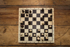 A single hand playing chess on a wooden board set on some wooden. Wooden chess board set on some old wooden floor. check mate in place Stock Images