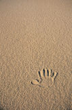 Single hand print in beige sand Stock Images
