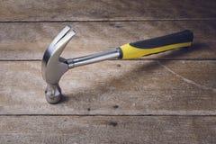 Single handed worn sledge hammer on grunge wood Royalty Free Stock Photos