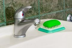Handle mixer tap with drop of water. Single handle mixer tap mounted on a wash basin with drop of water on background of a wall with green tiles Royalty Free Stock Image