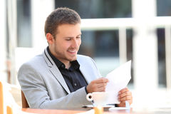 Happy executive reading a letter in a bar Royalty Free Stock Image