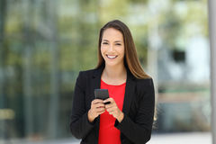 Happy executive holding phone looking at you. Single happy executive wearing suit and holding phone looking at you on the street Stock Photography
