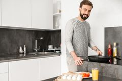 Single happy man wearing casual clothing cooking dinner on fryin Royalty Free Stock Photos