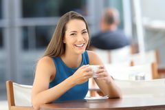 Woman posing looking at you in a coffee shop. Single happy woman posing holding a cup looking at you sitting in a coffee shop terrace Stock Images