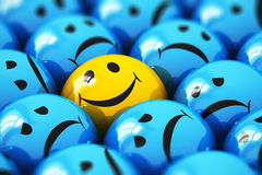 Single happy yellow smiley among blue sad ones. Creative abstract success and people emotion concept: macro view of happy yellow smiley face ball icon or button stock illustration