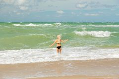 Girl in sea surf. Single happy young woman in swimsuit walking at sea surf with splashes royalty free stock image
