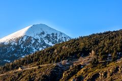 Single high mountain with pick in snow, blue sky and green forest in front, Andorra, Pyrenees royalty free stock image