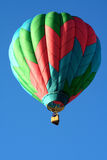 Single Hot Air Balloon. A colorful hot air balloon soars in a beautiful blue sky Stock Image