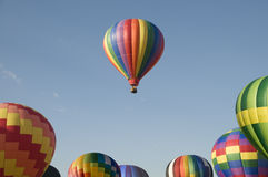 Single hot-air balloon floating above a balloon festival Stock Images