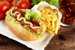 Single hotdog with french fries on tray with cola on plank Stock Photo