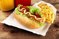 Single hotdog with french fries on tray on plank Royalty Free Stock Images