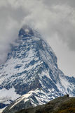 Single house in front of mountain. Single, lonely small house in front of the vertical rock wall of mountain Matterhorn in Switzerland Stock Image