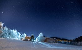 Single house and night lights with starry sky stock images