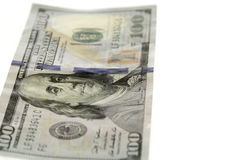 Single Hundred Dollars Bill. Bill laying flat on white background, focus on Benjamin's eyes Stock Photo