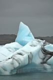 Single iceberg against dark sky. Iceberg against threatening sky at Jokulsarlon glacier lake in Iceland Stock Image