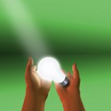 A single idea. Spotlight on lit bulb held in hands Stock Image