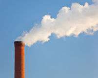 Single industrial brick smokestack. Tall industrial brick chimney venting gasses into the atmosphere Royalty Free Stock Images
