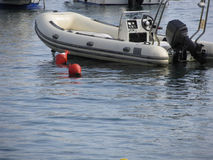 Single inflatable dinghy with outboard motor lies at anchor in a harbor . Tuscany, Italy Royalty Free Stock Photography