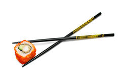 Single japan sushi roll in the chopsticks Royalty Free Stock Photo