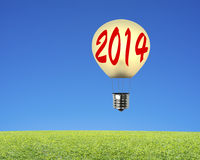 Single lamp balloon with 2014 flying over meadow, sky background Royalty Free Stock Photo