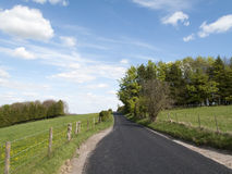 Single lane country road. Through countryside and farmland Stock Photo