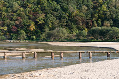 Single lane log bridge over a shallow river Royalty Free Stock Photos