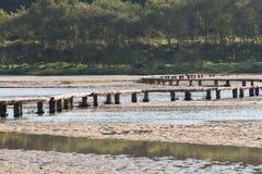 Single lane log bridge over a shallow river Royalty Free Stock Photo
