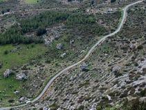 Single lane mountain dangerous road and white car. Royalty Free Stock Photo