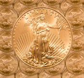 Single Liberty gold coin. Gold Eagle one ounce coins in a patterns and stacked on each row with a single Liberty coin on the top stock image