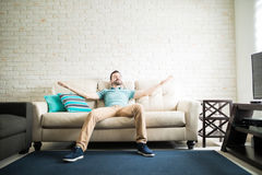 Single lifestyle. Latin single man relaxing alone in the living room of his new apartment with her arms open Royalty Free Stock Photo