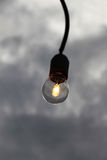 Single light bulb against a cloudy sky Stock Photos