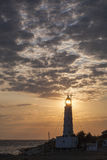 Single lighthouse under clouds and sun lighting through lamp of lighthouse Stock Photos