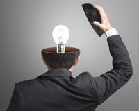 Single lighting lamp inside businessman head. In gray background Royalty Free Stock Images