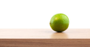 Single lime with droplets on a wooden plank. Stock Image