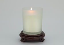 Single lit candle in glass on wood stand isolated on white backg Royalty Free Stock Photos
