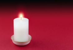 Single lit candle in gold rimmed white holder  on red. Single lit white candle in gold rimmed white holder  on red background Royalty Free Stock Photo