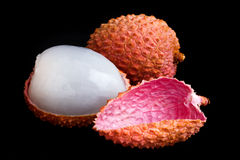 Single litchi with skin removed and flesh. On black Royalty Free Stock Image