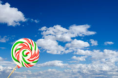 Single sugar lollipop in white green and red on background of sk Royalty Free Stock Photos