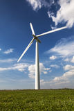 Single, Lone Wind Turbine against a blue, cloud-strewn sky Royalty Free Stock Image