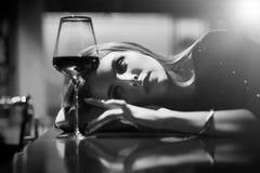 Girl in bar. Single luxury beautiful woman sitting with wine near bar in restaurant, monochrome stock photos