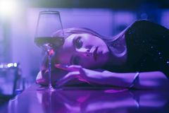 Girl in bar. Single luxury beautiful woman sitting with wine near bar in restaurant, ultraviolet toned image stock photography