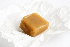 SIngle luxury unwrapped caramel toffee on white wrapper in persp Royalty Free Stock Image