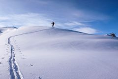 A single male back country skier skiing along a long snow ridge. On his way to a remote alpine peak Royalty Free Stock Photography
