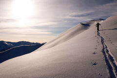 Single male backcountry skier climbing a snowy ridge near Klosters. In the Swiss Alps Stock Photos