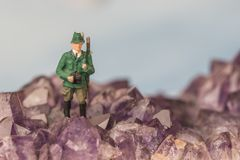 Scenic view of miniature hunter figure in shape of a hiking person in the mountains and blue sky. Royalty Free Stock Photo