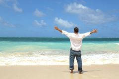 Single male standing on beach facing ocean Stock Photography