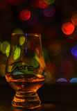 Single malt tasting glass, single malt whisky in a glass, bokeh. Background, party night royalty free stock photography