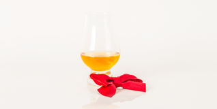 Single malt tasting glass, single malt whisky in a glass, white. Background, red bow, exclusive set stock photo