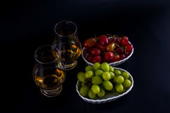 Single malt tasting glasses, single malt whisky in a glass, whit. E and red grapes in white bowls, black background stock images
